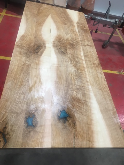 A table top made from Olive Ash also with blue epoxy resin running through it.
